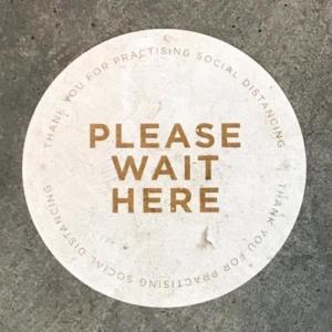 """Please wait here"" signage on floor"
